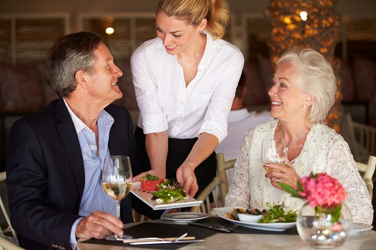 Waitress Serving Food To Senior Couple In Restaurant